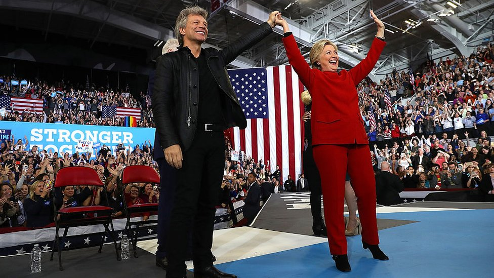 Hillary Clinton with Jon Bon Jovi at rally, in red pantsuit