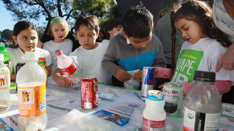 School children look at a display showing how much sugar is in soft drinks and juices