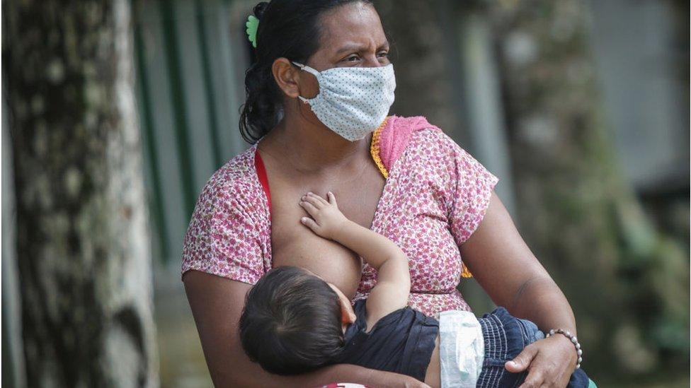 Mujer con mascarilla amamantando en Brasil