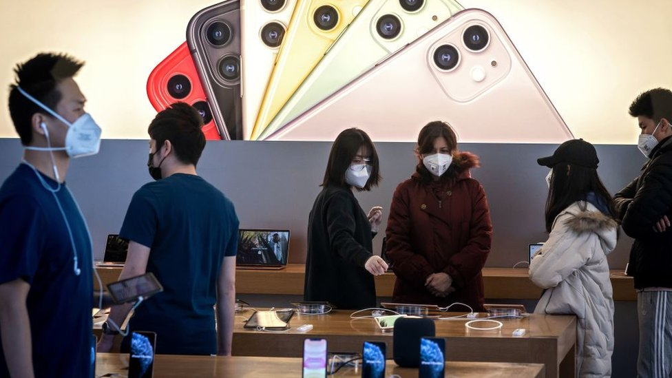 Personal y clientes de Apple con máscaras en una tienda en Pekín.