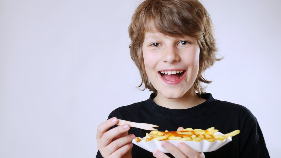 Niño comiendo papas fritas con kétchup