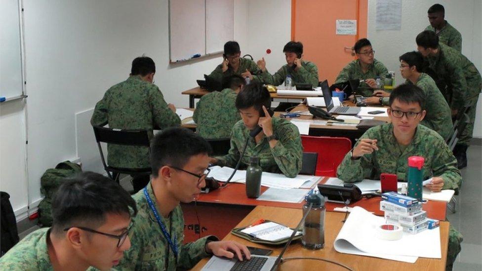 Personal militar en Singapur haciendo llamadas