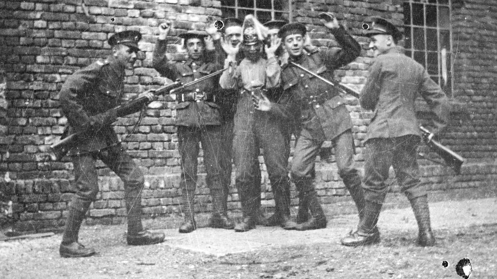 Soldiers dressed as the enemy pretending to get captured by colleagues in 1919