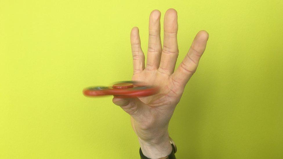 Fidget spinner balancing on one thumb