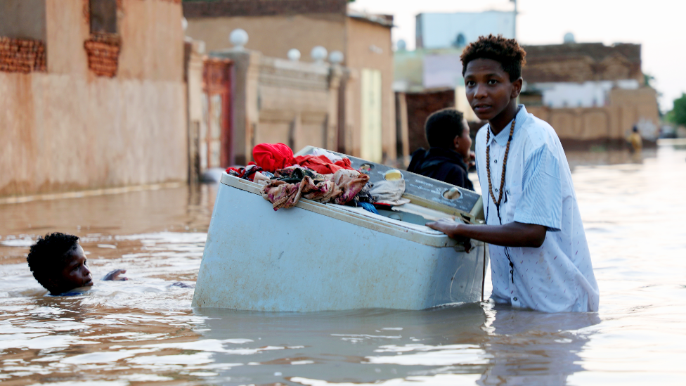 Someone rescuing a washing machine in floods near Khartoum, Sudan - September 2020