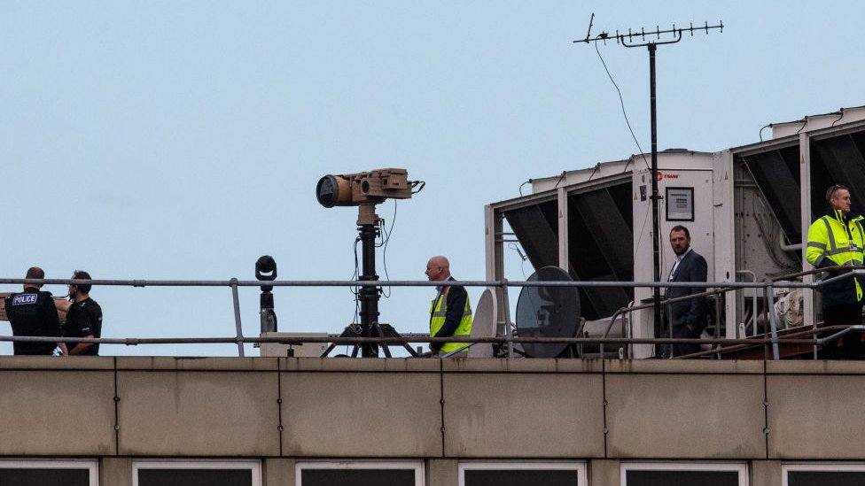Police and officials on roof of Gatwick with anti-drone devices