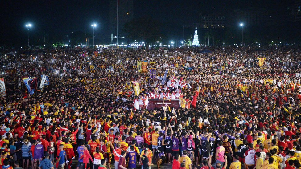 A huge crowd of devotees surrounds the Black Nazarene statue in Manila