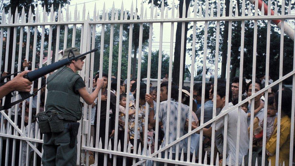Infantes de la Marina de EE.UU. resguardan la entrada de la embajada en Saigón, mientras una multitud de vietnamitas espera ser evacuada