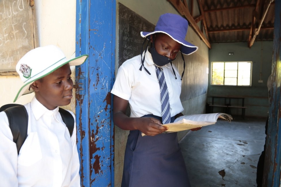 Two shy-looking secondary school students in uniform look at a textbook.