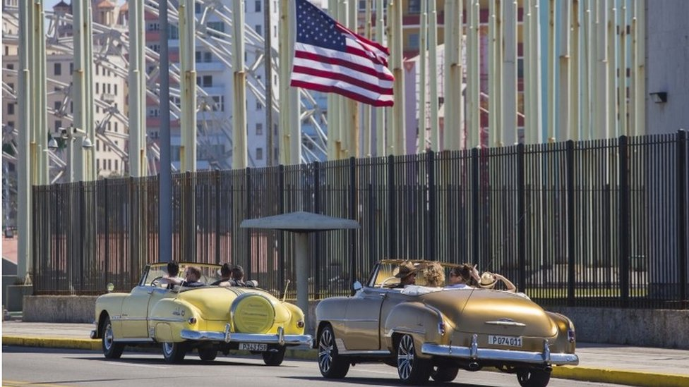 Tourists ride vintage American convertibles as they pass by the United States embassy in Havana, Cuba