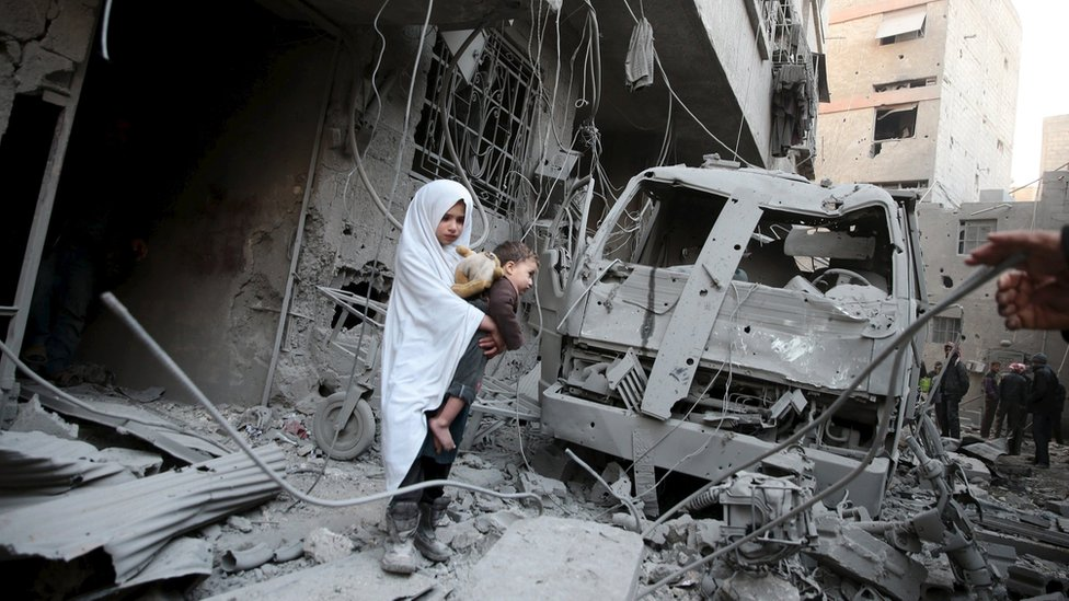 A girl carries a baby at the site of what activists said was a government air strike in Douma, in the eastern suburbs of Damascus (10 January 2016)