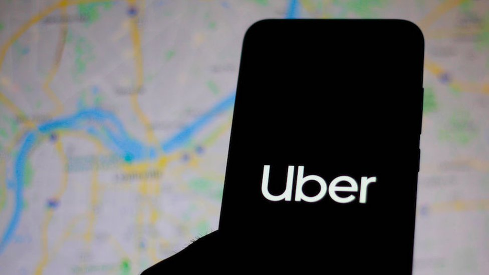 silhouette of phone with Uber logo, map background