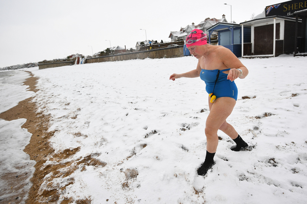 An early morning swimmer walks down a snow-covered beach at Thorpe Bay, Essex, on 9 February 2021