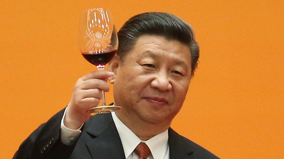 President Xi Jinping raises a glass of wine from a podium, set against a yellow background, in this photo