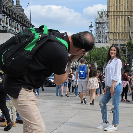 A man bending over to take a woman's photograph