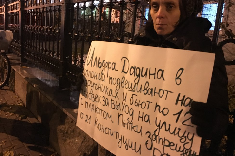 "Woman holding sign saying ""They hang Dadin by his handcuffs and 12 men beat him for taking to the streets with a protest banner. Torture is banned under Article 21 of the Russian constitution"