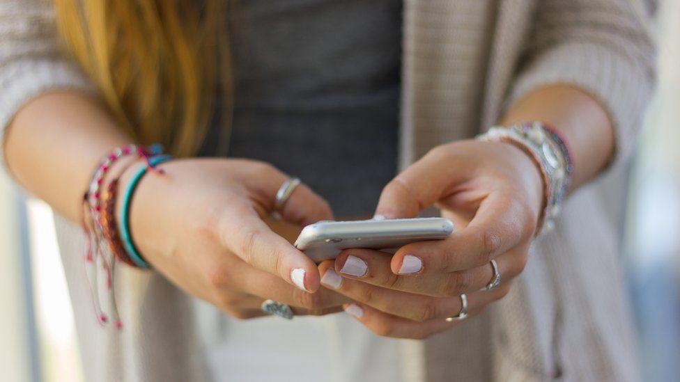 Mujer con un celular en la mano