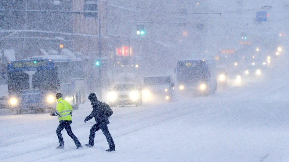 People cross a snow covered road on February 3, 2012 in Helsinki