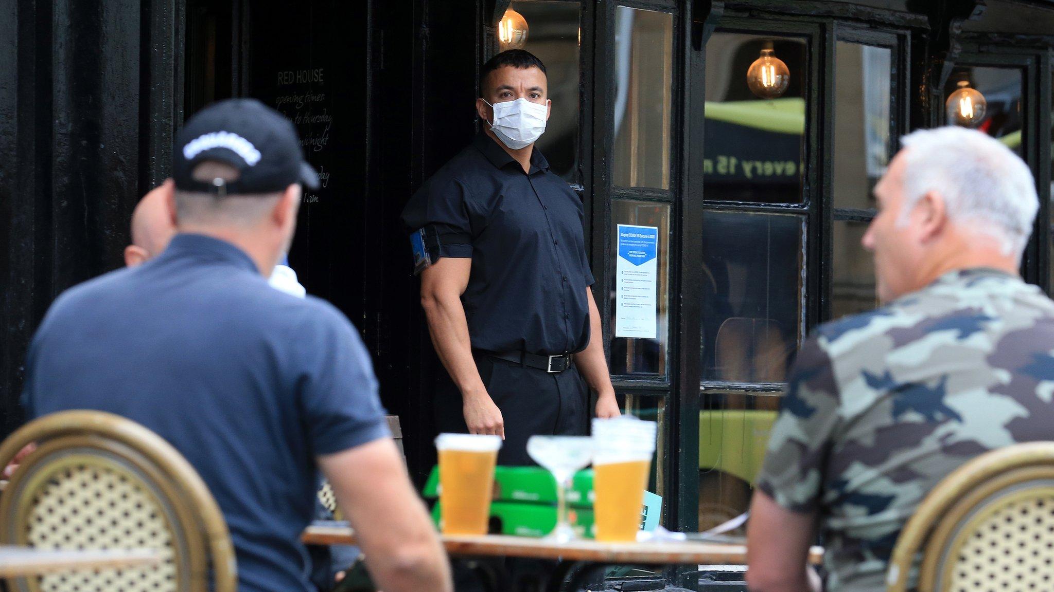 Un portier portant un EPI (équipement de protection individuelle), un masque facial ou une couverture par mesure de précaution contre la propagation du COVID-19, se tient en service alors que les clients sont assis avec leurs boissons dans un pub rouvert à Newcastle