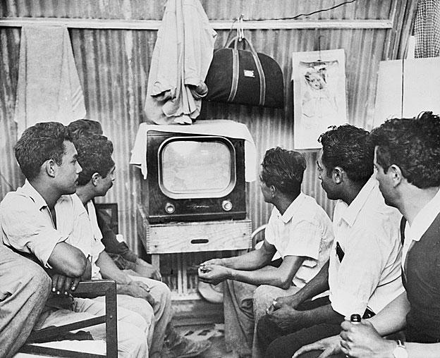 En sus humildes barracas después de un duro día de trabajo, los braceros se relajan mirando la televisión. Los hombres juntaban sus ganancias para comprar el set.