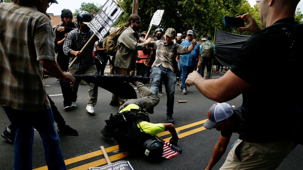 a woman kicks a man who is on the ground clutching a US flag