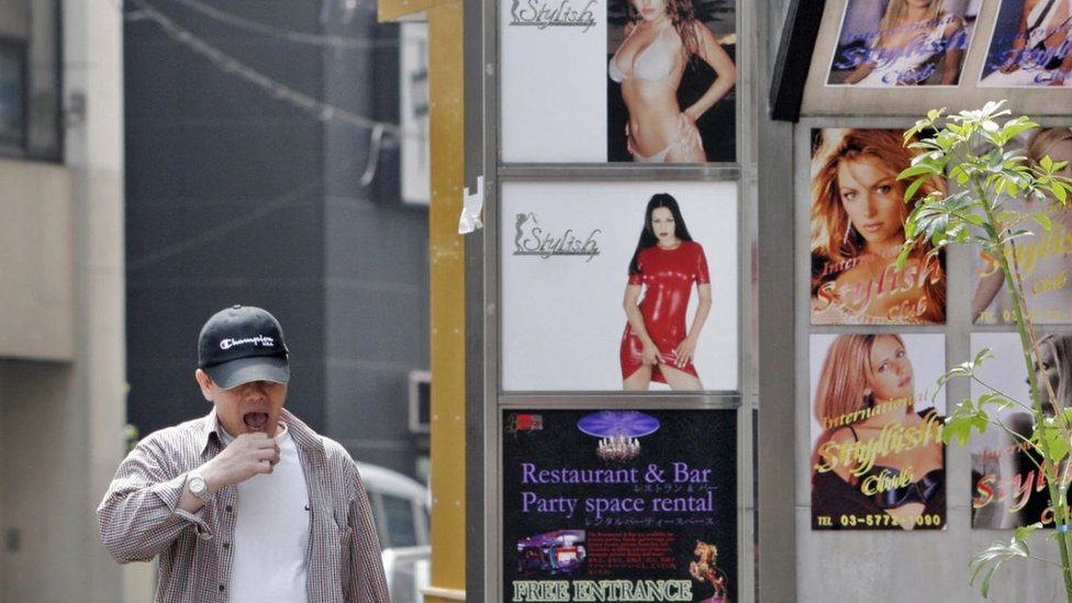 Un hombre pasa por anuncios de clubes con fotos de mujeres.