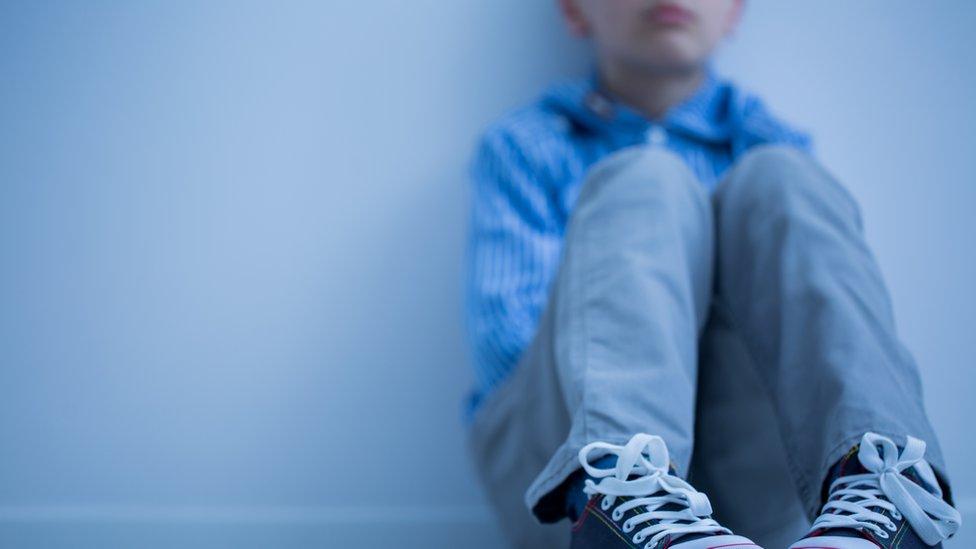 Un niño sentado en el suelo con gesto serio (imagen difuminada(