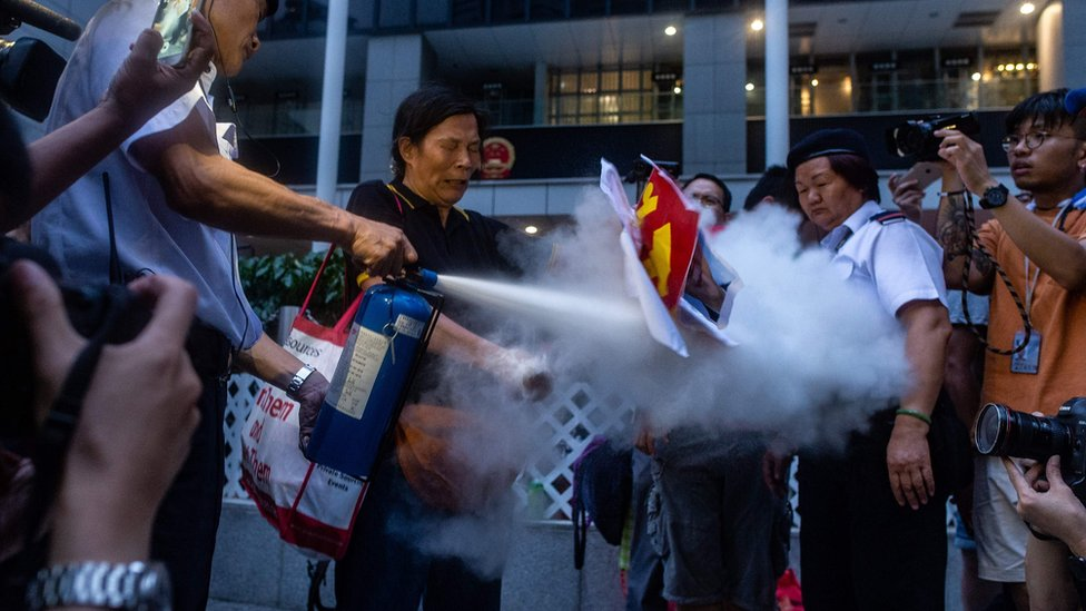 Security guard (L) extinguishes a burning portrait of Chinese leader Xi Jinping held by pro-democracy activist Lui Yuk-lin (2nd L) in Civil Square outside the Central Government Complex after attending a protest march by thousands in Hong Kong on July 1, 2018