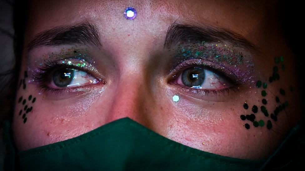 Joven con un pañuelo verde aguarda con lágrimas en los ojos afuera del Congreso argentino sobre el aborto