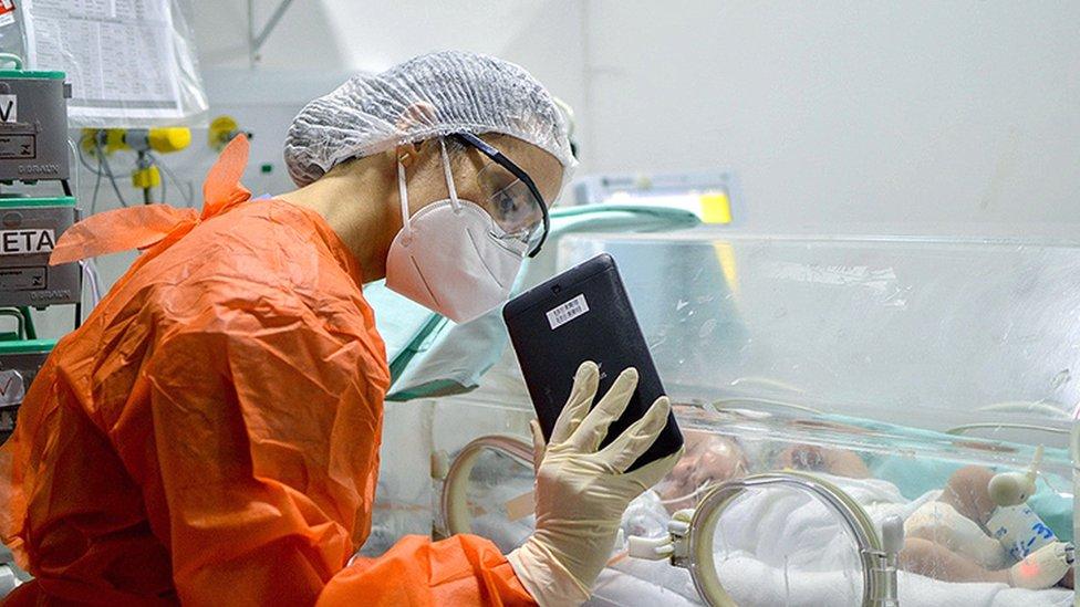 Médica muestra a un bebé a través de videollamada