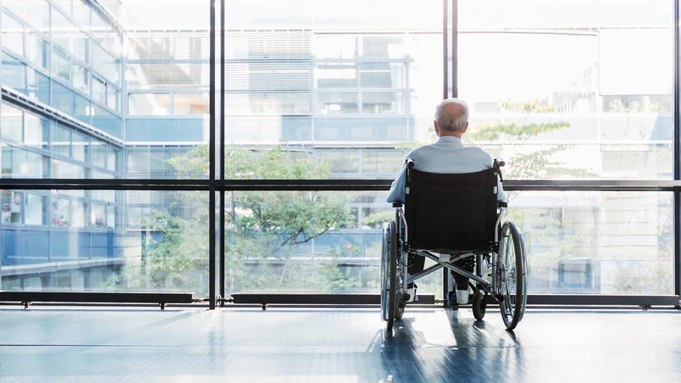 An old man in a wheelchair looking out of a window in an office corridor