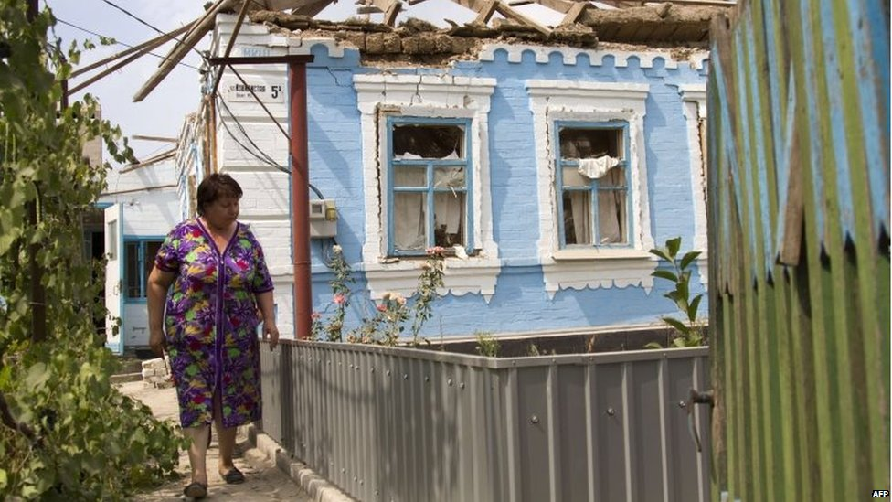 A resident walks in front of her house destroyed by shelling perpetrated by pro-Russian separatists in the village of Sartana, near Mariupol (17 August 2015)