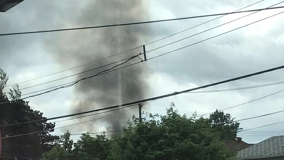 A plume of smoke rises over houses in Kamloops