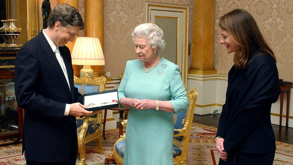 Queen Elizabeth II presents Bill Gates with his honorary knighthood at Buckingham Palace, alongside his wife Melinda, in London 2015