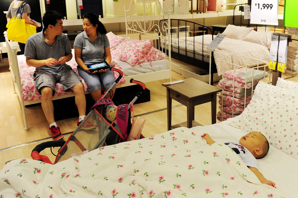 A young Chinese couple wait as their baby sleeps on a display bed, as they shop at an Ikea furniture store in Beijing on 15 August 2011