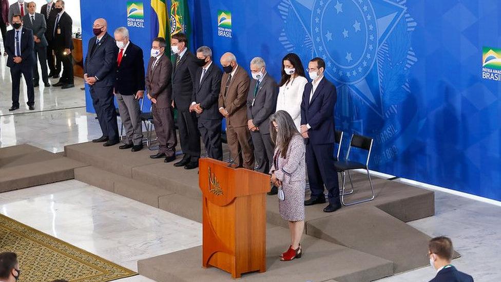 Foto com ângulo amplo mostra Bolsonaro e vários participantes do evento em pé e com cabeça baixa