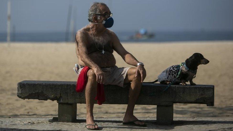 رجل يرتدي كمامة يجلس ومعه كلب على مقعد حجري على شاطئ برازيلي، 17 مايو/أيار 2020