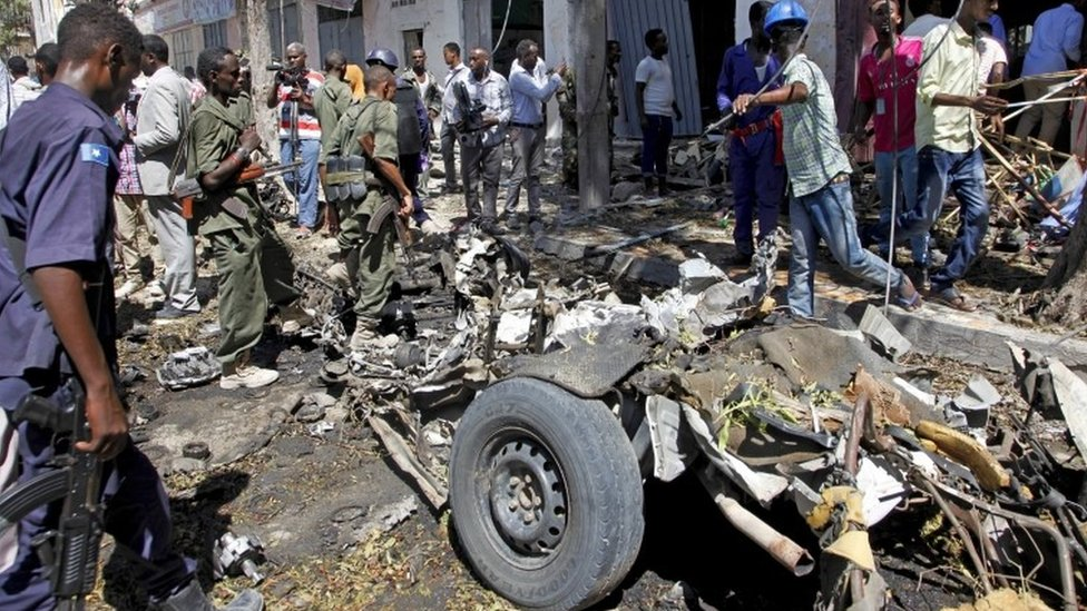 Security forces and others inspect the scene of a car bomb attack in the capital Mogadishu, Somalia Monday