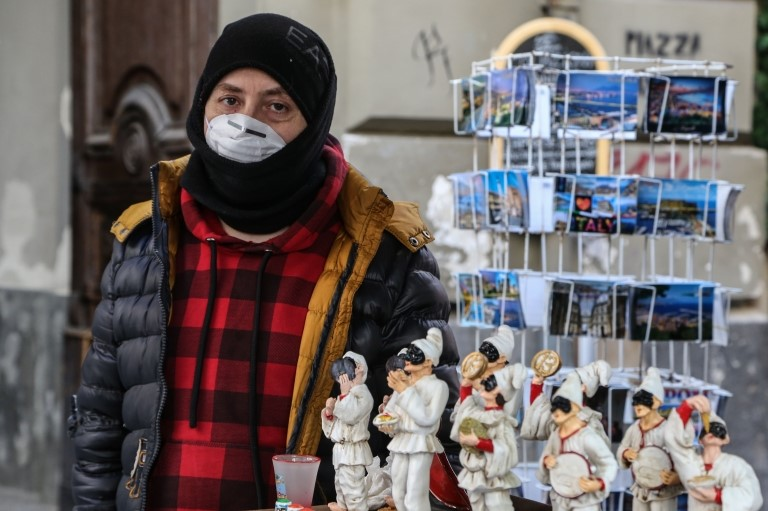 A vendor wears a respiratory mask in Naples