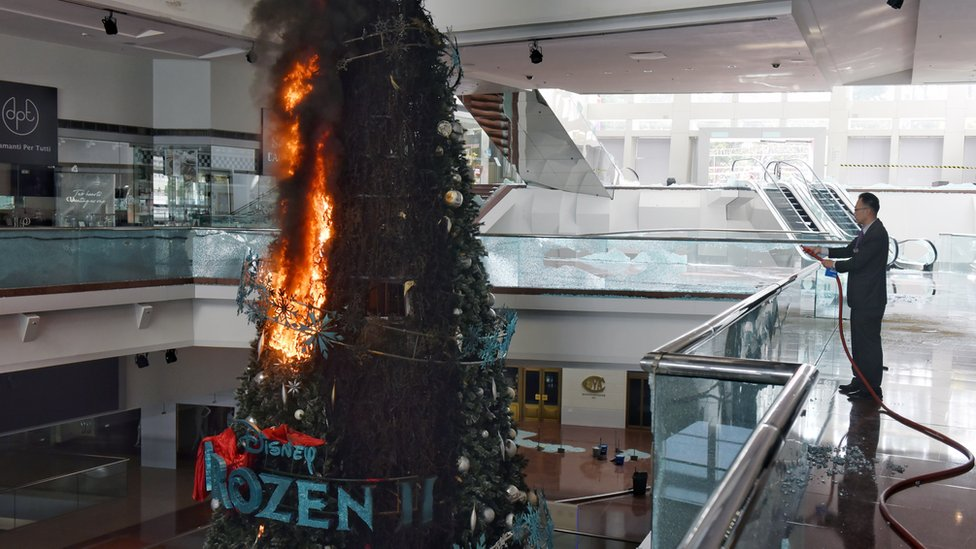 A person tries to extinguish a burning Christmas tree after protesters set fire to it at Festival Walk shopping mall in Kowloon Tong, Hong Kong, China, 13 November 2019. Hong Kong is in its sixth month of mass protests that were originally triggered by a now withdrawn extradition bill, which have since turned into a wider pro-democracy movement.