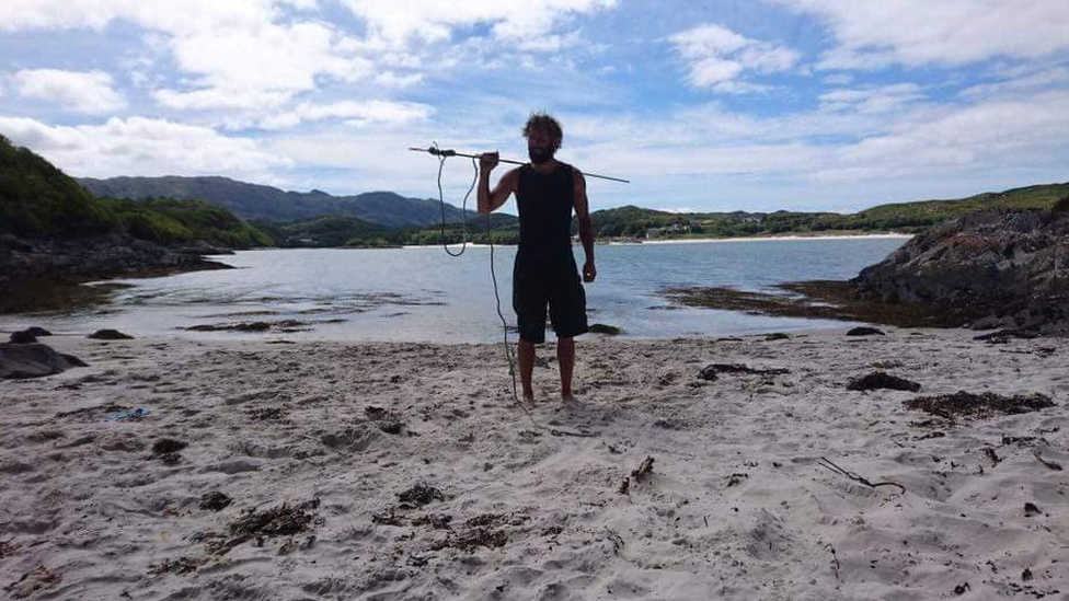 Chris on a beach with a fishing spear