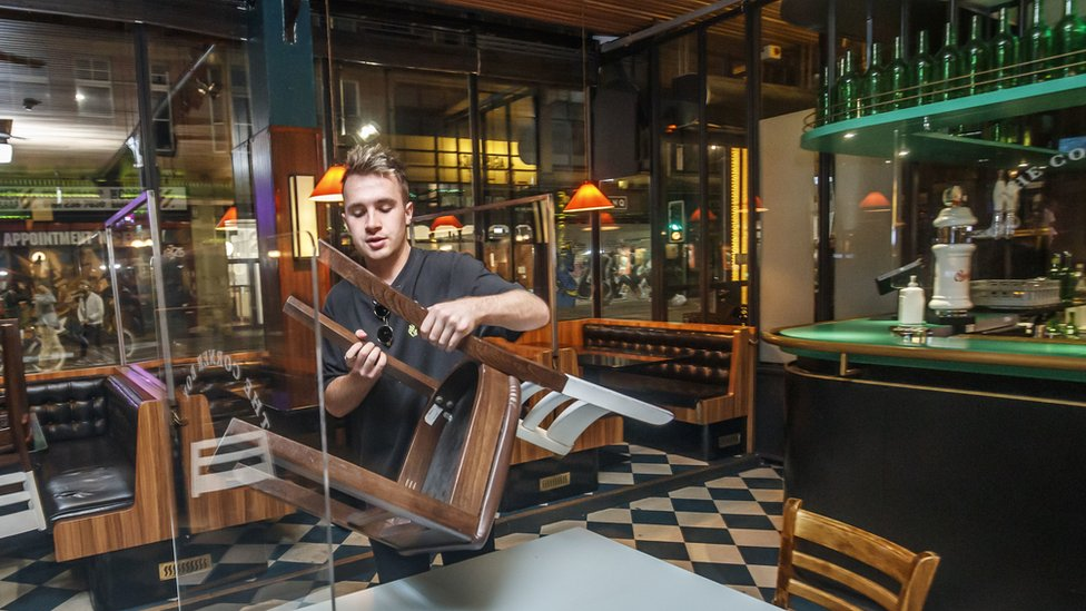 A bar tender in a pub in Manchester puts away chairs at the end of the evening