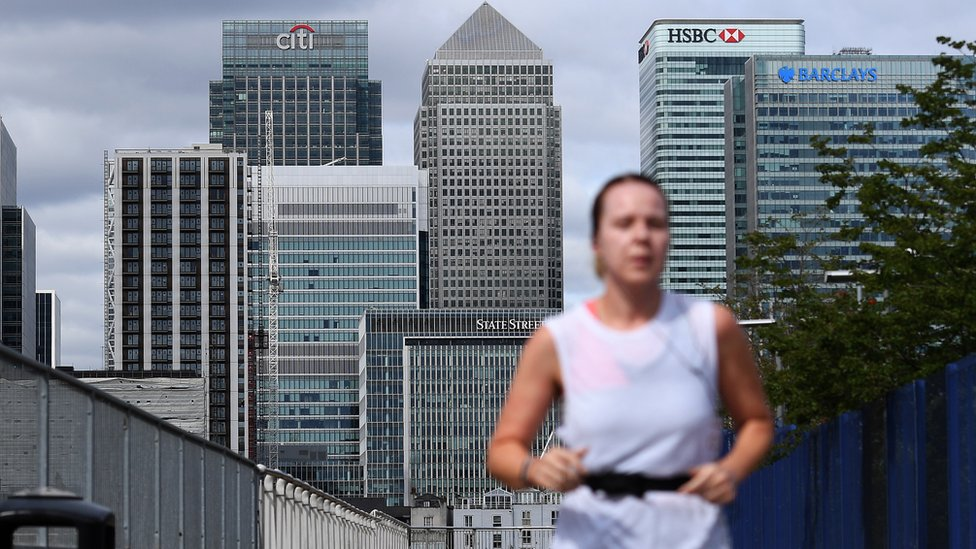 A jogger runs past offices at Canary Wharf in central London
