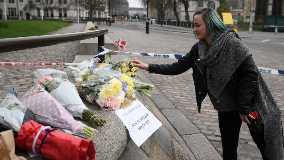 A woman lays flowers near the scene of the attack