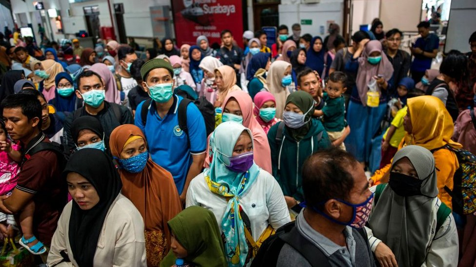 Indonesians wear masks at transport hub.