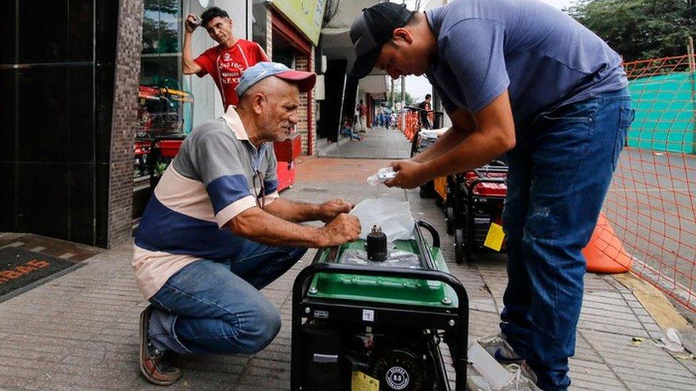 Dos venezolanos prueban un generador en una tienda de Cúcuta