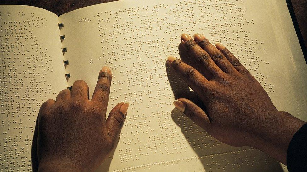 Manos que leen un libro en braille.