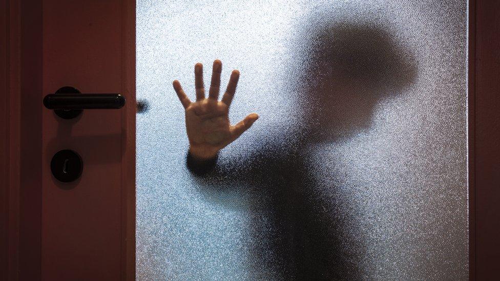 Un niño apoya la mano detrás del vidrio de una puerta.
