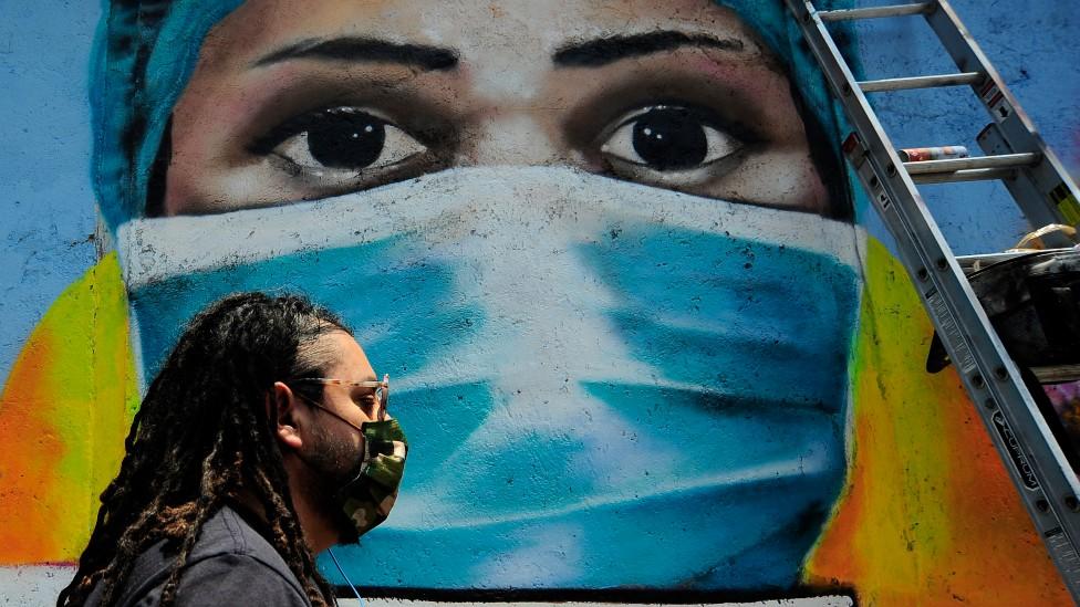 Un hombre camina delante de una pared con un mural