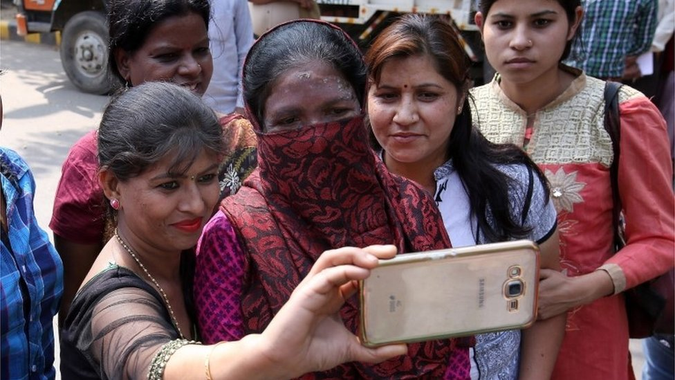 Indian women activists take selfie with Soni Sori (C) as they participate in a protest march on the occasion of International Women's Day in Delhi on 8 March